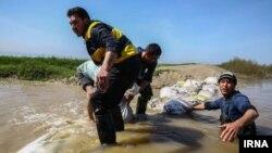در تصویر: شهروندان در حال کمک به ساختن سیلبند در مناطق سیلزده گمیشان و روستای خواجهنفس