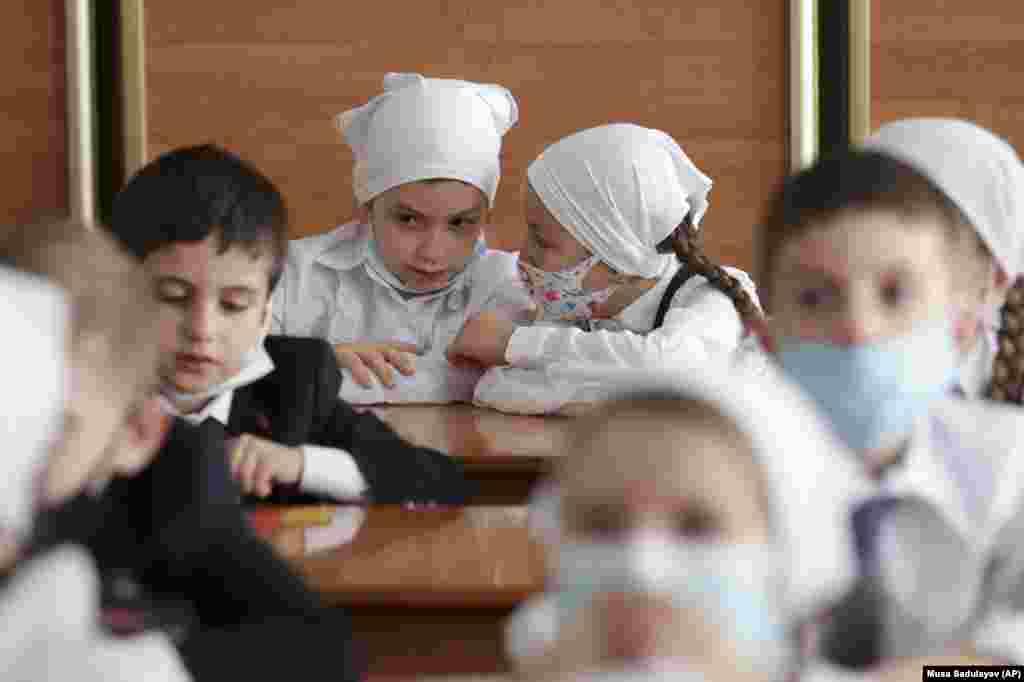Учні в масках для обличчя сидять у класі під час церемонії Дня знань, присвяченої початку занять у столиці Чечні Грозному 1 вересня