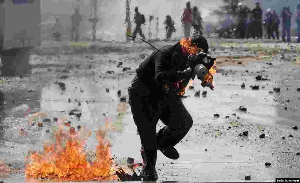 A protester runs from a petrol bomb explosion during a clash with Turkish riot police on Istanbul's Taksim Square on June 11 amid ongoing antigovernment demonstrations.
