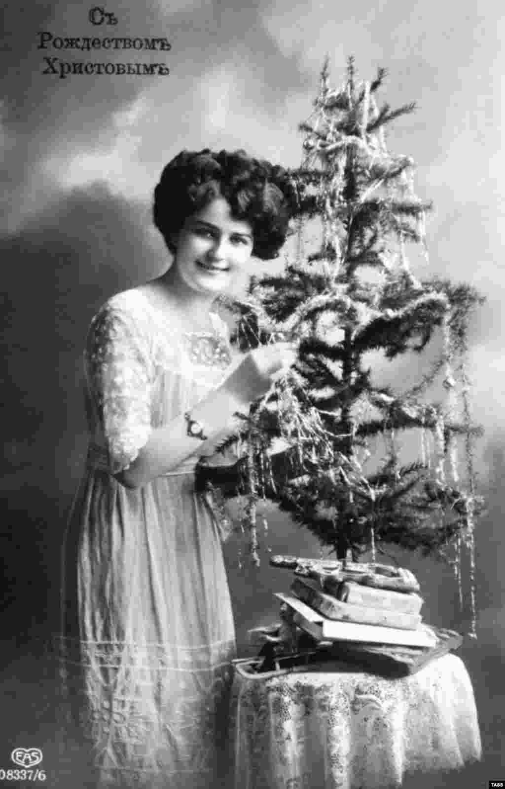 "A 1912 Christmas postcard of a woman and her pint-sized tree. Christmas traditions such as the decorated tree were introduced to Russia from Europe around 200 years ago, and were gradually taken up by Russia's wealthy. But the lower classes were apparently less fond of the custom. Pravda, the Soviet propaganda mouthpiece, reported that each year workers' children ""peered enviously through the window at the fir tree glittering with multicolored lights and the rich children who were merry around it."""