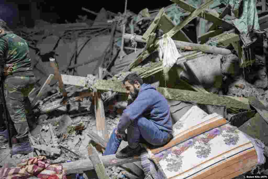 Сидящий на руинах житель. Спасатели ищут под завалами его родственников после того, как ракета попала в жилой район в Гяндже, втором по величине городе Азербайджана. 17 октября 2020 года.