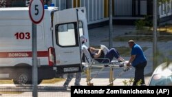 Medical workers transport a patient suspected of having COVID-19 to a hospital in Moscow on June 26.