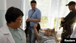 Interim Kyrgyz leader Roza Otunbaeva (left) talks to a patient wounded during ethnic clashes as she visits a hospital in Jalal-Abad today.