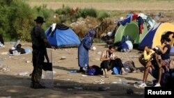 Шекара маңында мигранттардың жанында тұрған македониялық әскери адам. (Көрнекі сурет)
