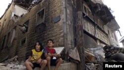 Сириянын Хомс шаарындагы талкаланган үйдүн жанында отурган балдар