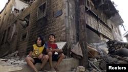 Сурия. Хомс шаҳри болалалри уруш туфайли вайрон бўлгануйлари олдида ўтиришибди.