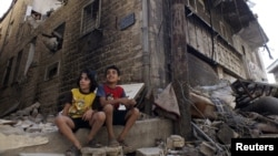 Syria - Children sit along a damaged street filled with debris in the besieged area of Homs September 19, 2013