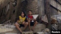 طفلان سوريان يجلسان على أعتاب مبنى مدمّر في حمص