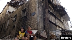 Сирийские дети перед разрушенным зданием в Хомсе