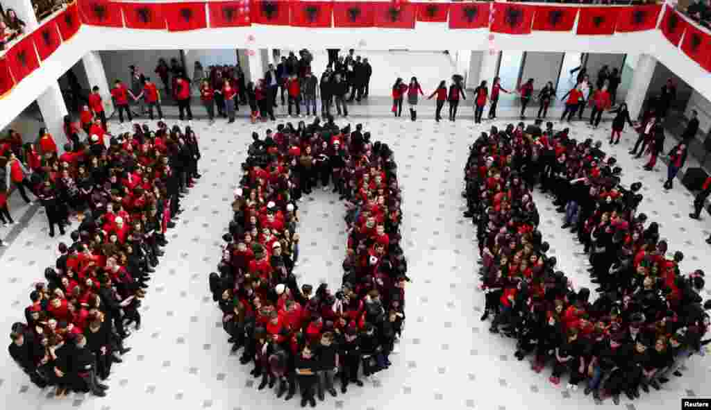 Pupils from the Xhevdet Doda secondary school in Pristina, the capital of Kosovo, form the number 100 in the colors of the Albanian flag.