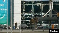 Солдат стоїть біля вибитих вибухом вікон аеропорту Брюсселя, 22 березня 2016 року