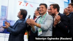 Ukrainian President Volodymyr Zelenskiy (center) reacts at his party's headquarters in Kyiv as parliamentary results come in on July 21.