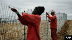 Африқои Ҷанубӣ - Коргарон садди байни Африқои Ҷанубӣ ва Зимбабверо таъмир мекунанд. 18 марти соли 2008.