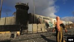 Шабуылға ұшыраған Рамаллах қаласының көшесінде кетіп бара жатқан палестиналық әйел. 25 шілде 2014 жыл