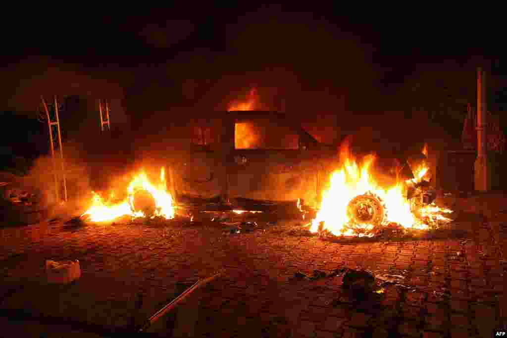 Vehicles are engulfed in flames after they were set on fire inside the U.S. Consulate compound.