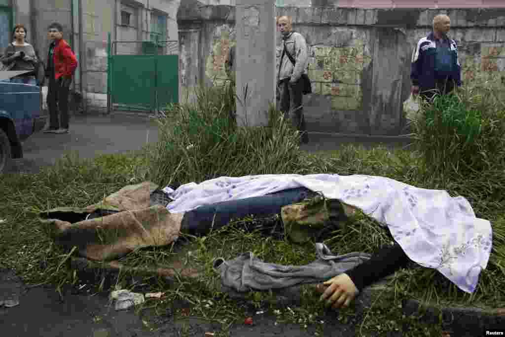 9 мамыр күні Украинаның шығысындағы Мариуполь қаласында әскерилер мен ресейшілдер арасында шайқас болды. Украина ішкі істер министрі Арсен Аваков қақтығыстан 20 шақты сепаратист өлгенін хабарлады. БірақДонецк облыстық денсаулық сақтау департаменті Мариупольде ресейшіл сепаратистерге қарсы арнайы операция барысында тоғыз адам қаза тауып, 42 адам жараланып ауруханаға түскен деген мәлімет берген. Мариупольдегі шайқас кейінгі күндері де жалғасты. Суретте: Үкімет күштері мен сепаратистер арасындағы шайқастан соң милиция мекемесі жанында беті жабық жатқан адам денесі. Мариуполь, 9 мамыр 2014 жыл.