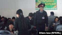 Тамақ ішіп отырған жазасын өтеушілерді күзетіп жүрген полиция қызметкері. Шымкент, 27 қазан 2015 жыл. (Көрнекі сурет)