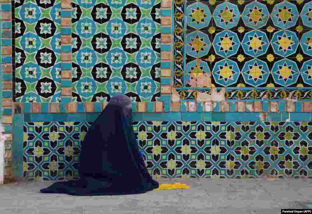 "A burqa-clad Afghan woman sits in the courtyard of the Hazrat-e Ali shrine, or ""Blue Mosque,"" in  Mazar-e Sharif during the holy month of Ramadan. (AFP/Farshad Usyan)"