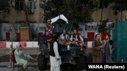 Afganistan: një grup talibanësh qëndrojnë pranë një automjeti ushtarak në Kabul, më 1 shtator, 2021.