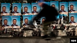 A man rides his bicycle past election posters of former Prime Minister and VMRO-DPMNE leader Nikola Gruevski in Skopje.