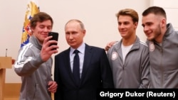 President Vladimir Putin (second left) poses for a selfie during a meeting on January 31 with Russian athletes and team members who will take part in the upcoming Winter Olympic Games as neutral athletes.