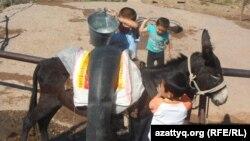 Дети села Амангельды Казыгуртского района Южно-Казахтанской области пополняют запасы воды, 21 сентября 2014 года.