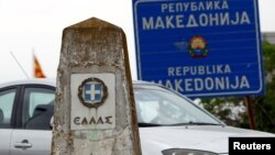 A car travels past a Greek border stone and a sign on the border of Macedonia and Greece.