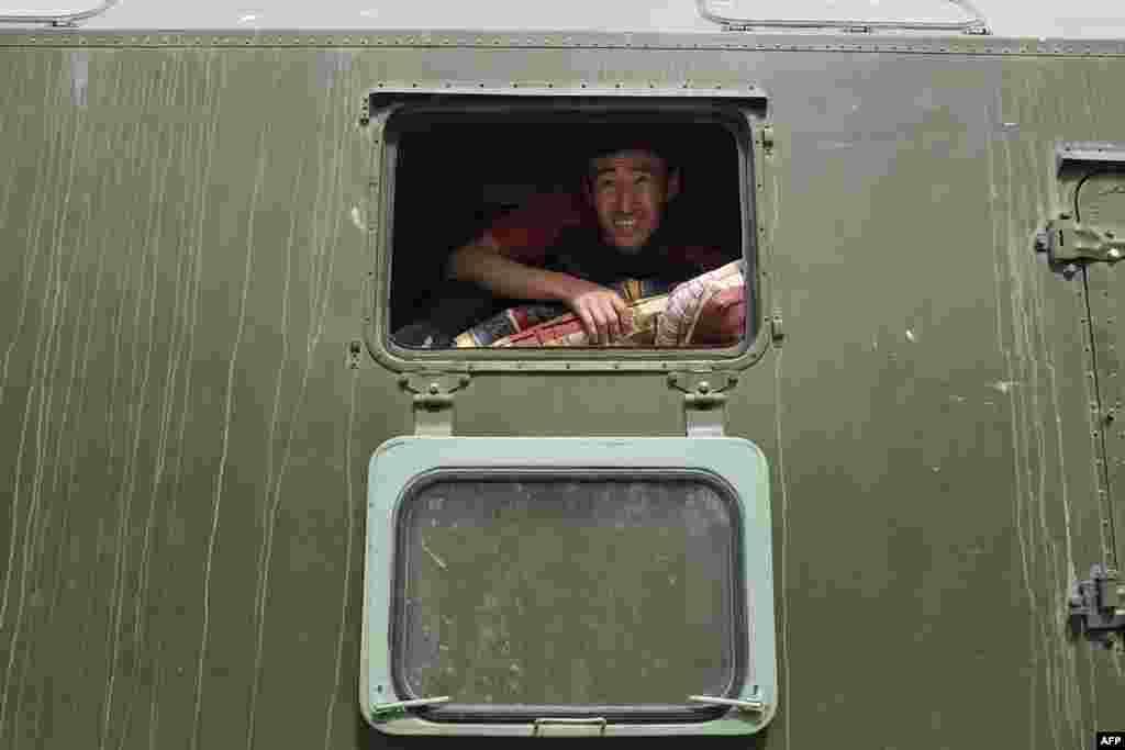 A Kyrgyz emergency worker unloads mattresses for people evacuated after violent clashes along the Kyrgyz-Tajik border. (AFP)