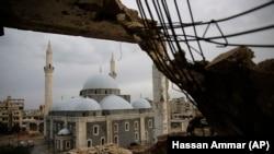 Разрушенное здание на фоне мечети в Хомсе, городе в Сирии. Январь 2018 года.