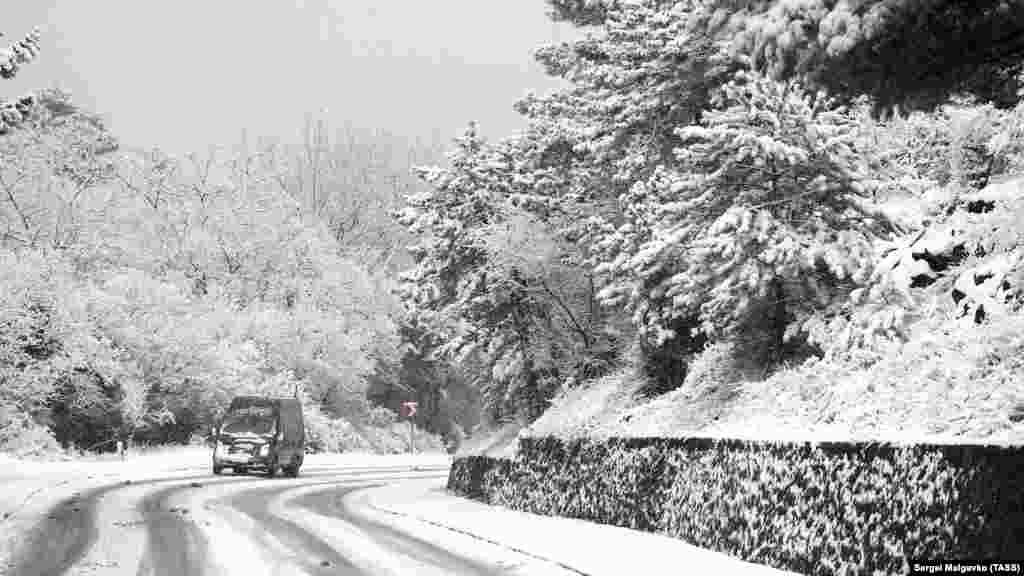 Занесеною снігом дорогою неподалік від Гаспри пробирається автомобіль