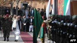 Transition Commission Chairman Ashraf Ghani Ahmadzai (second from left) and Afghan Defense Minister Abdul Rahim Wardak (far left) inspect an honor guard during a ceremony to assume security control in the city of Charikar in Parwan Province on December 1.