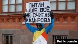Орусиядагы оппозициянын өкүлү плакат кармап турат