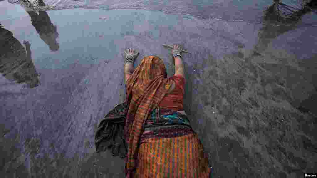 A Hindu devotee prostrates herself in the sands near the Arabian Sea as she worships the Sun god during the Hindu religious festival Chhat Puja in Mumbai, India. During the festival, Hindu devotees worship the Sun god and fast all day for the betterment of their family and society. (Reuters/Vivek Prakash)
