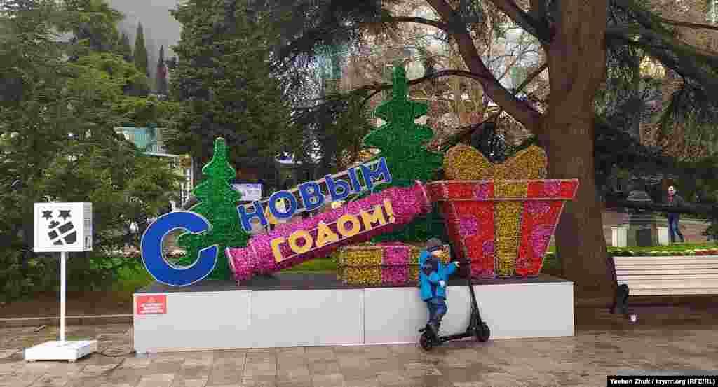 Ребенок с самокатом у новогодней инсталляции