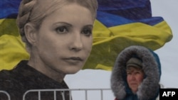 A woman walks in front of a giant poster bearing a picture of jailed Yulia Tymoshenko and a Ukrainian flag on Independence Square in Kyiv