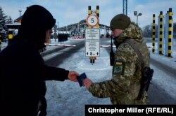 A Ukrainian border guard officer checks the passport of a Ukrainian man traveling to Russia through the Hoptivka border on November 29.