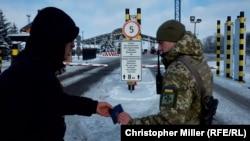 Український рикордонник перевіряє документи на пункті пропуску Гоптівка. 29 листопада 2018 року