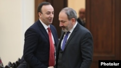 Armenia -- Prime Minister Nikol Pashinian (R) and Constitutional Court Chairman Hrayr Tovmasian shake hands ahead of a 2018 meeting in Yerevan.