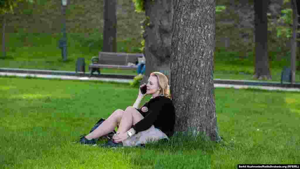 Девушка говорит по телефону на газоне в парке«Владимирская горка»