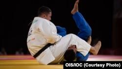 Бекарыс Садуақас (ақ формада) олимпиада ойындарында. 9 қазан 2018 жыл.