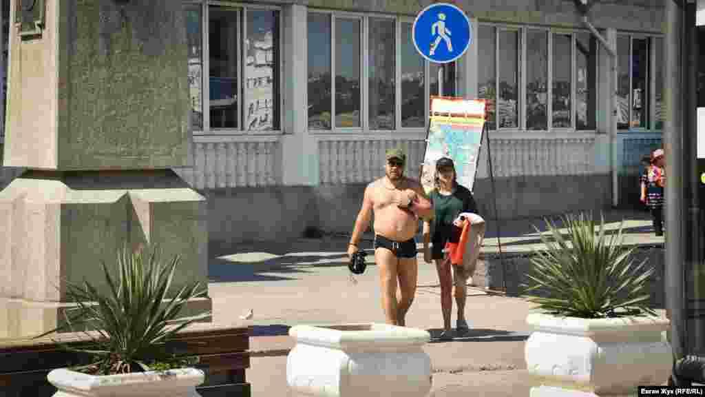 На набережной Адмирала Перелешина в Артиллерийской бухте изнемогают от жары и прогуливаются в купальных костюмах