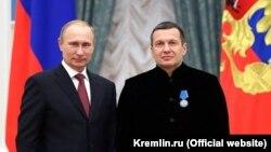 Vladimir Putin (solda) teleaparıcı Vladimir Solovyovu Kremldə ordenlə təltif ediləndən sonra