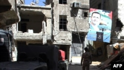 A man walks under a portrait of Syrian President Bashar al-Assad in a street inside the Yarmouk Palestinian refugee camp in the Syrian capital on April 6.