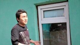 Гражданин Китая Ян Шаолян стоит возле разбитого окна офиса редакции газеты «Жас Алаш». Алматы, 30 марта 2010 года. Фото предоставлено редакцией газеты «Жас Алаш».