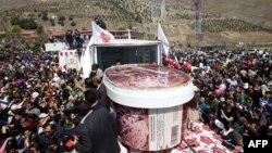 Люди собрались вокруг двухметровой емкости с мороженым, которое изготовлено иранским производителем молочной продукции ко Дню Исламской Республики.