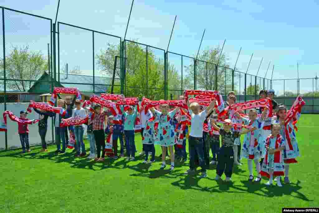 Воспитанники детского приюта благодарят за открытие спортивной площадки. В руках у них шарфы с надписью: Polska (Польша).