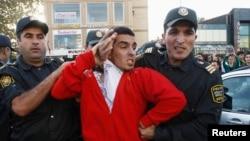 Полицейские ведут участника акции протеста оппозиции. Баку, 12 октября 2013 года.