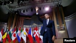 U.S. President Barack Obama waves after delivering a speech at Palais des Beaux-Arts in Brussels on March 26.