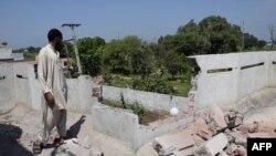 Пакистандыктар Индиянын куралдуу күчтөрүнүн артиллериялык чабуулунан кыйраган тамдын жанында турат. 28-август 2015