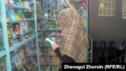 """Девушка рассматривает выставленную на продажу в магазине """"Муслима"""" религиозную литературу. Актобе, 9 января 2013 года."""